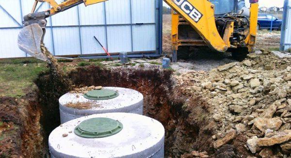 Финальная стадия работ по сооружения септика – окончательная засыпка грунтом котлована при помощи погрузчика
