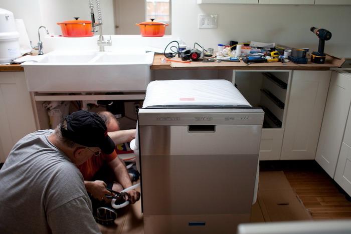 Процесс установки мастером посудомоечной машины